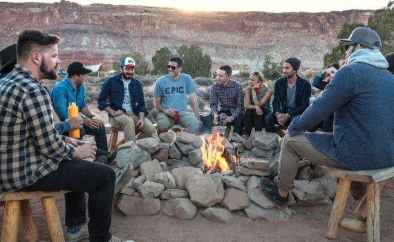 Junge Menschen sitzen rund um ein Lagerfeuer