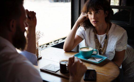 Ein Mann und eine Frau sitzen im Cafe und unterhalten sich