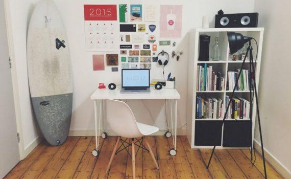 Zimmer mit Schreibtisch, Kalender und Surfbrett