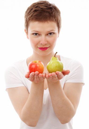 Frau hält Apfel und Birne in den Händen